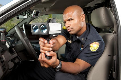 Police Officer checking vehicle speed with LIDAR gun